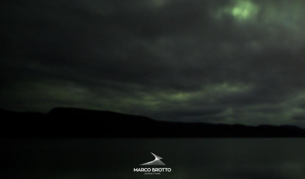 Aurora boreal com nuvens pesadas na Finlândia.