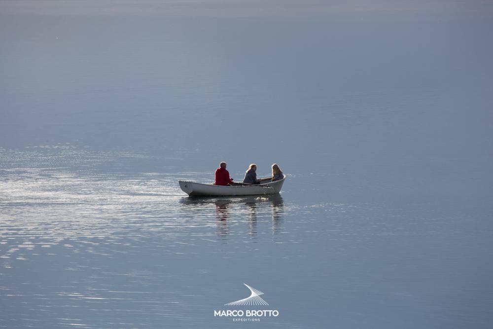 Jovens passeando no pequeno barco nas frias aguas dos fjords.